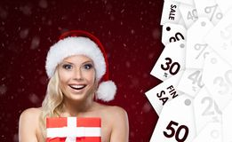 Pretty woman in Christmas cap hands present Royalty Free Stock Image