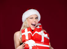Pretty woman in Christmas cap holds presents Stock Images