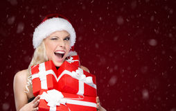 Pretty woman in Christmas cap holds a set of presents Royalty Free Stock Photos