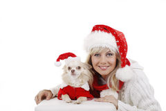 Pretty woman in christmas costume with dog. Pretty smiling woman beside her dog both in santa costume Royalty Free Stock Photo