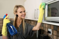 Pretty Woman Cleaning Kitchen Stock Photography