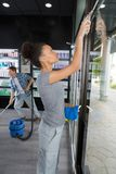 Pretty woman cleaning window at haridressers salon Royalty Free Stock Photos