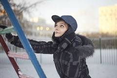 Pretty woman climbing on metallic ladder in winter Royalty Free Stock Image