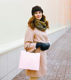 Pretty woman in coat with shopping bag in the city Royalty Free Stock Photography