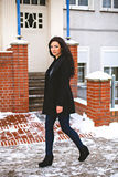 Pretty woman in coat walking on street Royalty Free Stock Photos