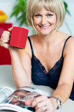 Pretty woman with a coffee mug in hand reading magazine Royalty Free Stock Photography