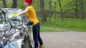 Pretty woman in colorful clothes washing black automobile car with soapy sponge. stock footage