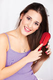 Pretty woman combing her hair Stock Images