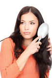 Pretty woman combing her long black hair Stock Photography