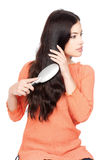 Pretty woman combing her long black hair Stock Images