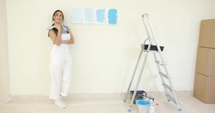 Pretty woman contemplating a choice of blue paint stock video