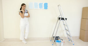 Pretty woman contemplating a choice of blue paint Royalty Free Stock Photo