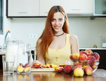 Pretty woman cooking beverages with peaches Royalty Free Stock Images