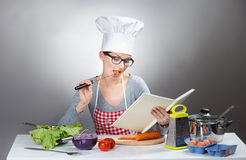 Pretty woman cooking with cookbook on gray background. Portrait of a young woman in chef's hat reading cookbook and cooking, gray background Stock Photo