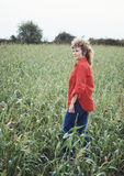 Pretty Woman in Corn Field. Pretty woman standing in and looking out over a field of corn Royalty Free Stock Images