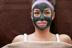 Pretty woman with cosmetic black mask on face Stock Photography