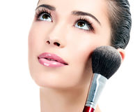 Pretty woman with a cosmetic brush Stock Images