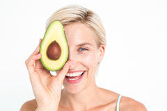 Pretty woman covering her eye with an avocado Stock Photos