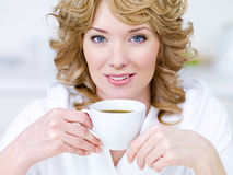 Pretty woman with cup of coffee. Close-up portrait of pretty young beautiful blond woman with cup of coffee Stock Images