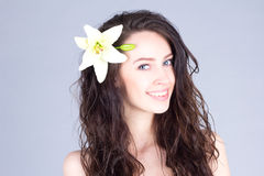 Pretty woman with curly brown hair and a flower in her hair smiling with teeth Royalty Free Stock Photos