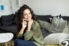 Pretty woman with curly hair sitting on the sofa in the room and stock image