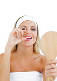 Pretty woman curving her lashes with mirror Royalty Free Stock Image