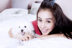 Pretty woman with cute dog on bed. Portrait of a pretty young woman with a cute Maltese dog smiling at the camera while lying on bed Stock Image