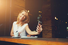 Pretty woman with cute smile making self photo on her smart phone during rest in cafe Royalty Free Stock Images
