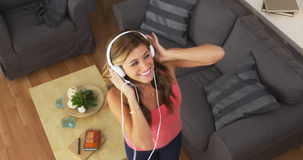 Pretty woman dancing to music with smartphone Stock Images