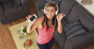 Pretty woman dancing to music with smartphone Stock Photo