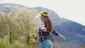 Pretty woman with dandelion wreath smiling and turning around with arms outstretched on mountains landscape. 4k stock video footage