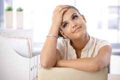 Pretty woman daydreaming in office. Pretty young woman sitting on chair in office, daydreaming Royalty Free Stock Photos