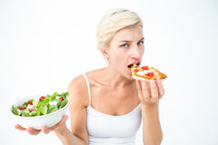 Pretty woman deciding eating pizza rather the salad Stock Photos