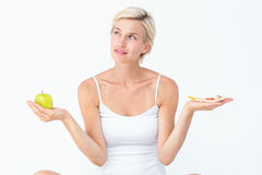 Pretty woman deciding between pizza and apple Stock Images