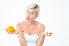 Pretty woman deciding between pizza and an orange Royalty Free Stock Photography