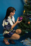 Pretty woman decorate a Christmas tree Royalty Free Stock Photography