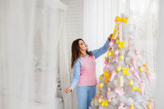 Pretty woman decorating fir-tree Stock Images