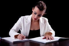 Pretty woman in desk with papers, writing Royalty Free Stock Photography