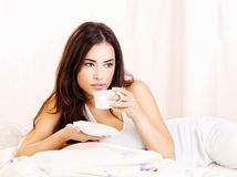 Pretty woman dink coffee in bed Royalty Free Stock Photos