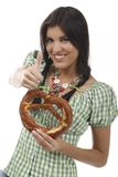 Pretty woman with dirndl and pretzel. Isolated on white stock image