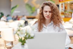 Pretty woman with dissatisfied expression works on laptop computer, being always busy, frowns face in displeasure, feels tired, we. Ars white blouse, spends free Royalty Free Stock Photography