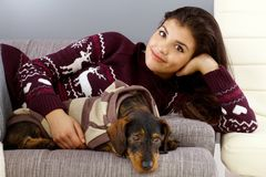Pretty woman with dog. Pretty woman lying on sofa with dog, smiling, looking at camera Royalty Free Stock Photography