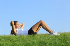 Pretty woman doing crunches on the green grass Royalty Free Stock Photos