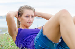 Pretty woman doing exercises for the abs. Stock Photography