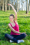 Pretty woman doing exercises in the park Stock Photo