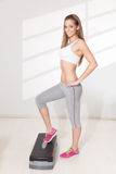 Pretty woman doing exercises on step Stock Images