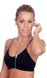 Pretty woman doing fitness listening music with headphones on whi Royalty Free Stock Photography
