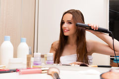 The pretty woman doing her hair preparing for party Royalty Free Stock Image