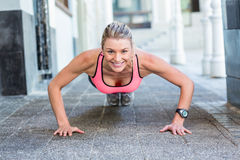 A pretty woman doing push-ups on the floor Stock Photography