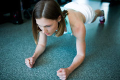 Pretty woman doing push-ups in the gym Stock Images